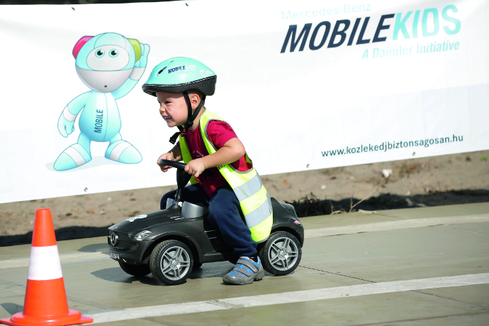A happy boy in a pedal car drives on a parcours. In the background you see a MobileKids banner.